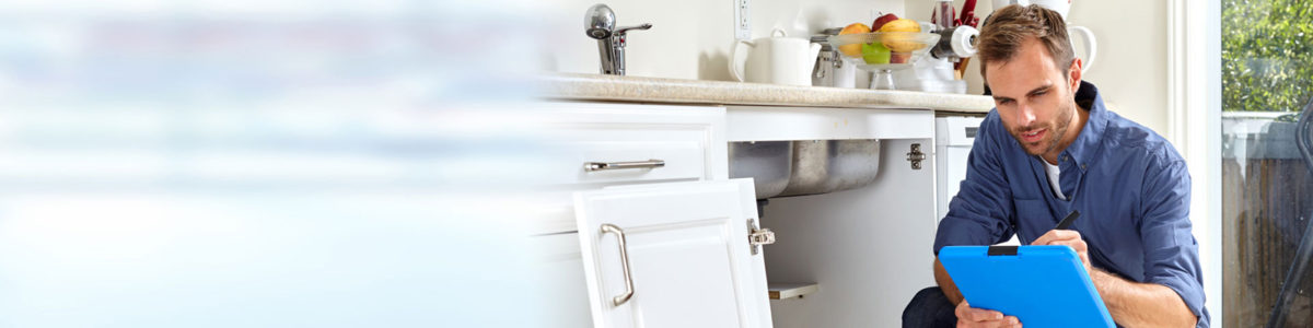 domestic plumber kneeling down next to kitchen sink