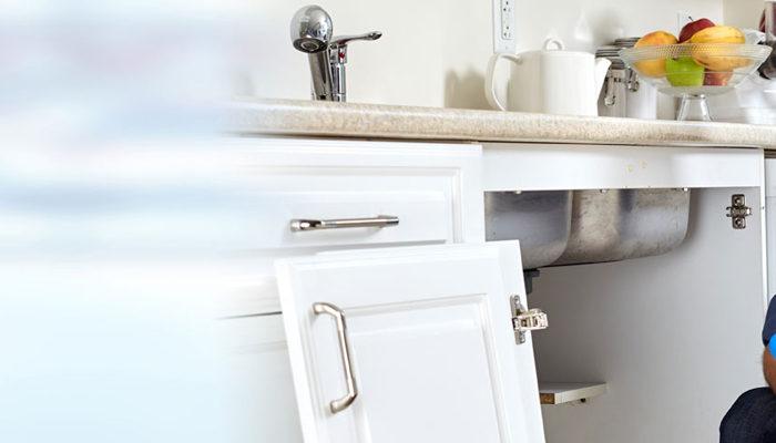 domestic plumber kneeling down next to kitchen sink