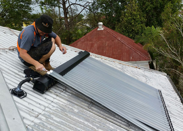 Plumber installing solar panels on roof